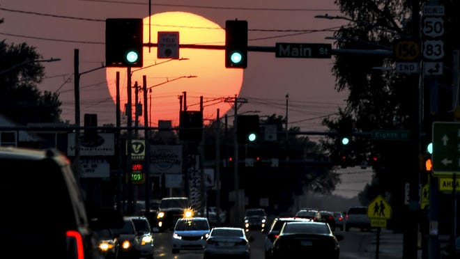 Motorist make their way along Kansas Avenue near dusk Wednesday as the sun appears larger, close to the horizon, and filtered from the smokey haze covering southwest Kansas from the western wildfires.