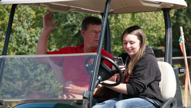Mikayla Combs-Wilber, a Milton High School sophomore, attempts to send a text while driving a golf cart. She was prompted by Bill Merrylees, a presenter for the Youth Safety Council of Vermont, who held a list of messages students could send.