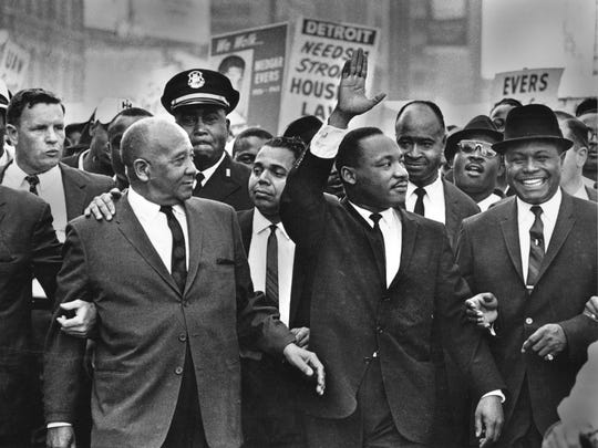 """The Rev. Martin Luther King Jr. waves to onlookers as he leads the 125,000 strong """"Walk to Freedom"""" on Woodward Avenue in Detroit  in 1963.  From left to right in the front row are: Walter Reuther, Benjamin McFall, Commander George Harge (cop with cap), Dr. King, and the Rev. C.L. Franklin."""