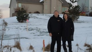 Mark and Lori May in the public right of way behind their home, where the lines will be built.