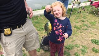 "Families fish at Glasgow Park Fishing Pond during the first ""Casting with Cops"" on Saturday, April 30. The event paired county police with young anglers and kicked off the opening of the fishing pond."