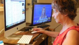 """Phyllis Krantzman, 71, of Austin, said buying her first computer when she was 62 """"thoroughly altered my entire life"""" because it helped her cope with the isolation that's resulted because of her insomnia. Krantzman says she """"loves TV and she loves her computer"""" and spends a lot of time online as she watches television. """"The computer is so important to me because I have so few people in my life,"""" she said. (Sharon Jayson for KHN)"""