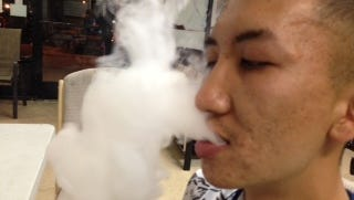 John Tran with a very thick, white vapor cloud exhaled from an electronic cigarette.