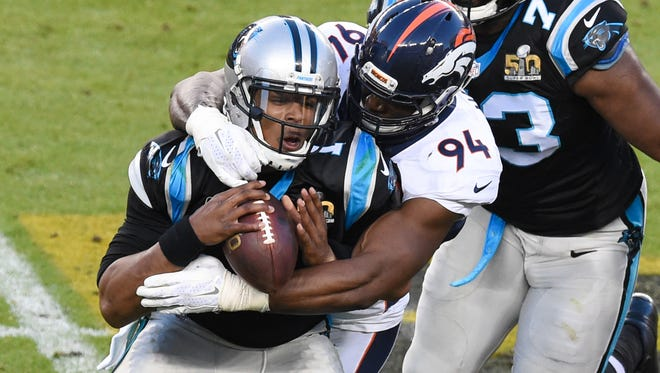 Carolina Panthers QB Cam Newton (1) is tackled by Denver's DeMarcus Ware.
