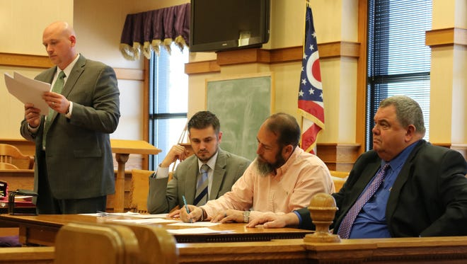 Thomas Owens, owner of Tom's Toys, signs his plea agreement prior to pleading guilty to three felony charges in Ottawa County Common Pleas Court on Thursday. He is joined by his attorneys, Patrick Mancinetti, left, and Tom DeBacco, right.