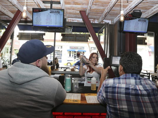 A bartender makes a drink at The Blind Burro, in San Diego, where the tequila prices can change every five minutes based on demand. The electronic Tequila Exchange boards, above, show the current prices for the bar's tequilas.