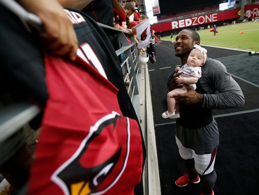 Cardinals CB Patrick Peterson poses with two-month-old Ariana Ortiz while signing autographs after practice during training camp at University of Phoenix Stadium in Glendale, Ariz. July 30, 2014.