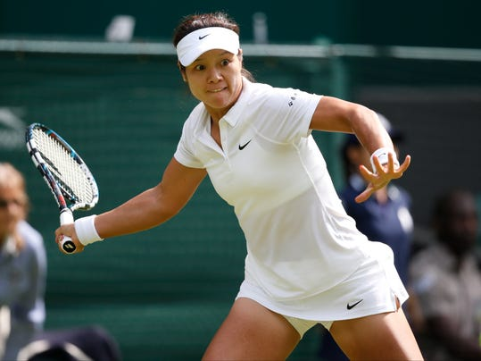 Li Na of China plays a return to Paula Kania of Poland during their first round match at the All England Lawn Tennis Championships in Wimbledon, London,  Monday, June  23, 2014. (AP Photo/Pavel Golovkin)