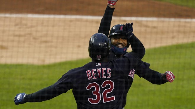 Cleveland Indians' Domingo Santana is greeted by Franmil Reyes after hitting a three-run home run during the fourth inning of a baseball game against the Detroit Tigers, Friday, Aug. 14, 2020, in Detroit.