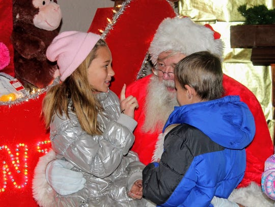 In this file photo from 2017, children sit on Santa's