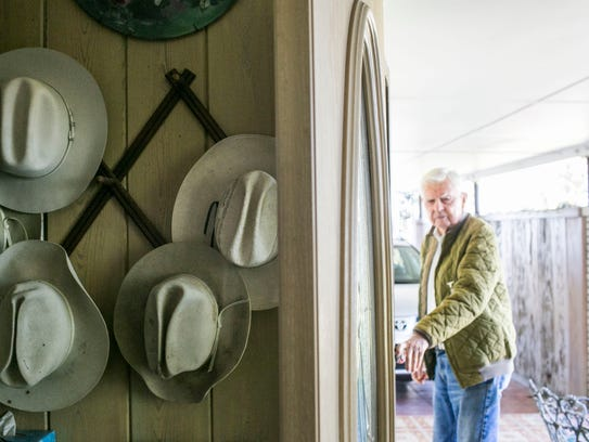 Bud Adams closes the door to his home near a collection