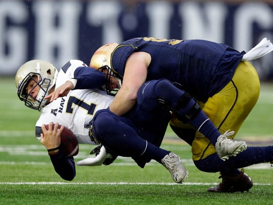 Navy quarterback Garret Lewis (7) is tackled by Notre Dame defensive lineman Jerry Tillery (99) during the first half of an NCAA college football game in South Bend, Ind., Saturday, Nov. 18, 2017. (AP Photo/Michael Conroy)