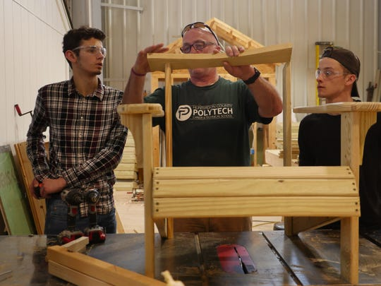 Charles Lachner, center, a teacher in Hunterdon County Polytech's construction program, directs students Jason Shapiro and Hunter Groelly on the fine art of building Adirondack chairs.