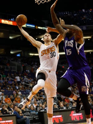 Phoenix Suns forward Jon Leuer goes in for a dunk against Sacramento Kings center DeMarcus Cousins during preseason NBA action at Talking Stick Resort Arena in Phoenix October 7, 2015.