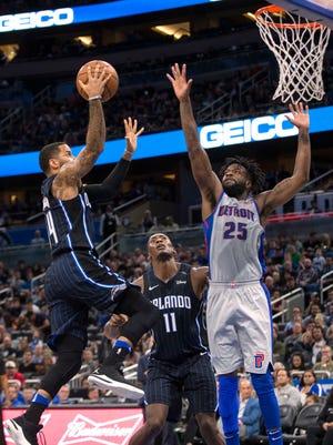 Magic guard D.J. Augustin, right, drives on Pistons forward Reggie Bullock during the first half on Thursday.