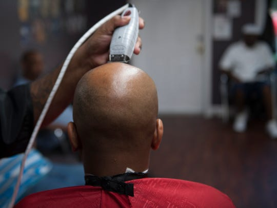 Mike Bryant shaves the head of Maurice Robinson at