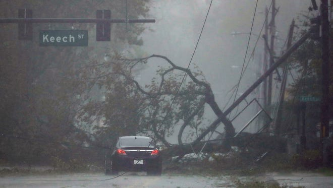 A car drives past a downed tree as Hurricane Matthew moves through Daytona Beach, Florida, on Friday.