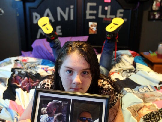 Danielle Eby, 10, holds a picture of her father, Daniel, who died of an overdose from cocaine and heroin on Oct. 4, 2013.