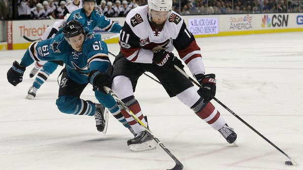 Arizona Coyotes center Martin Hanzal (11), from the Czech Republic, skates with the puck in front of San Jose Sharks defenseman Justin Braun (61) during the first period of an NHL hockey game in San Jose, Calif., Saturday, Feb. 4, 2017. (AP Photo/Jeff Chiu)