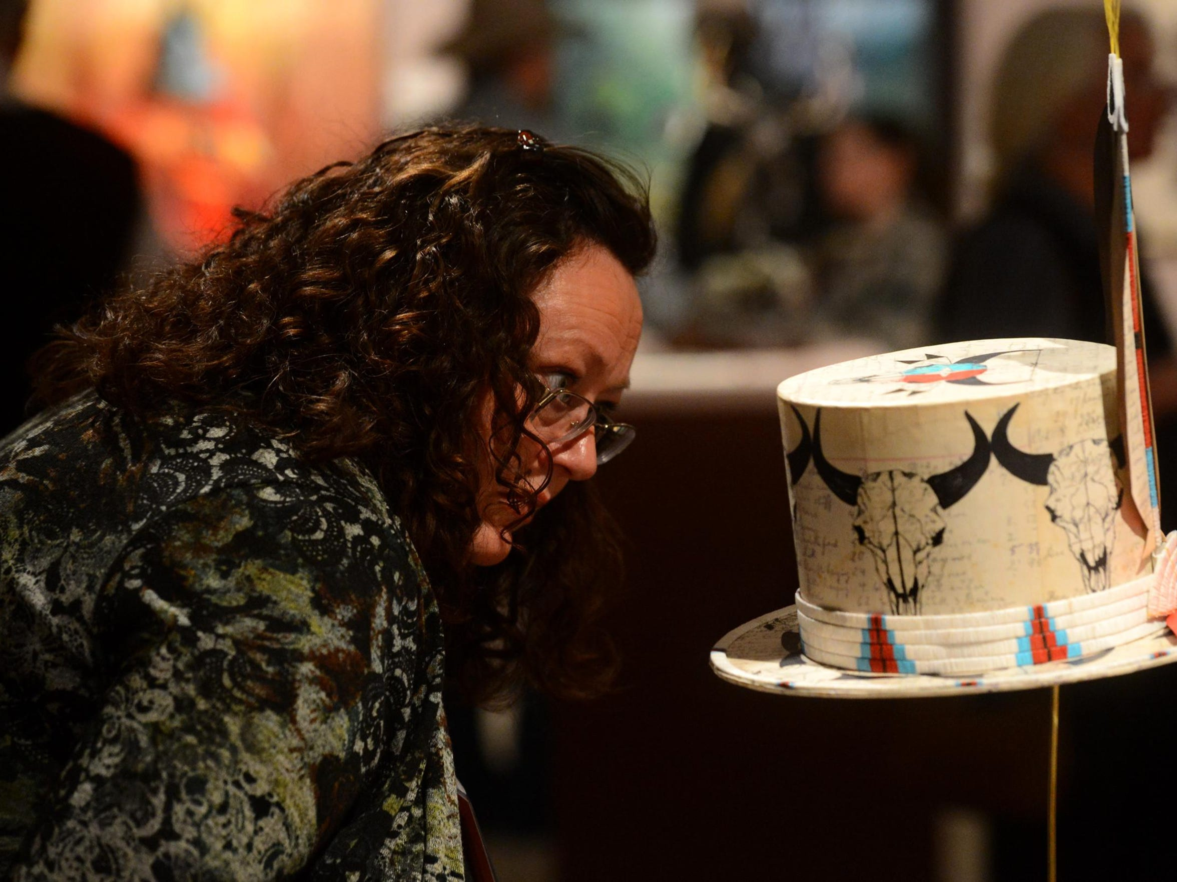 Jeanne Parker of Kalispell looks at a ledger art hat