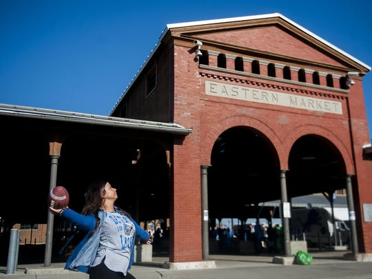 Lions fan Shelby Armstrong, 24, of Warren tosses a football while tailgating at Eastern Market.