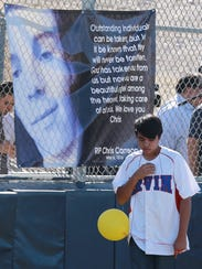 An Irvin baseball team member pays respects to Chapin