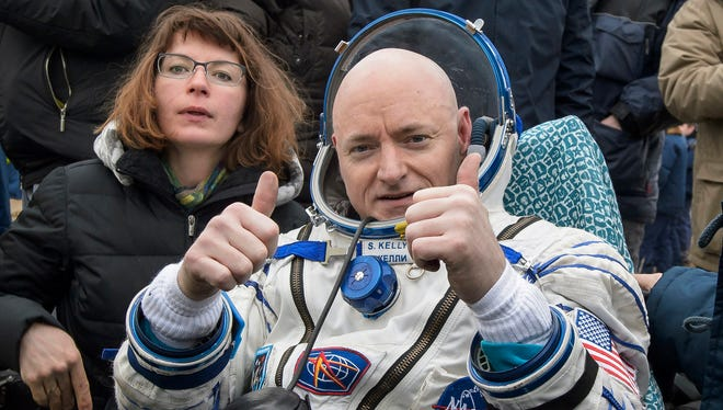 In this photo provided by NASA, International Space Station crew member Scott Kelly of the U.S. gestures after landing near the town of Dzhezkazgan, Kazakhstan, on Wednesday, March 2, 2016.
