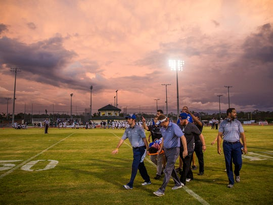 Paramedics and coaches carry Community School of Naples junior, Matthew Walther, off of the field on a stretcher on Friday, September 22, 2017 at Community School of Naples during the game against Moore Haven High School. Walther broke his leg during the first play of the game.