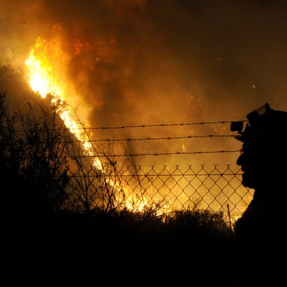 Firefighters watch the Thomas Fire burning near Shell
