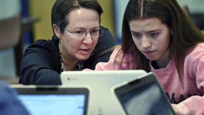 Jennifer Rocca, left, a teacher librarian at Brookfield High School in Connecticut, helps freshman Ariana Mamudi, 14, work on media literacy skills.