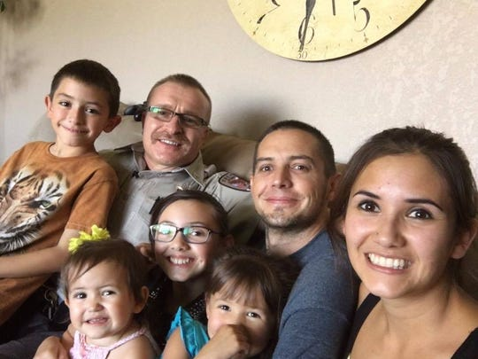 Otero County Sheriff's Office Court Security Supervisor Cpl. Theo O. Livingston sits with Josh Marchand's children at his home. Livingston is God father to two of Josh Marchand's children.