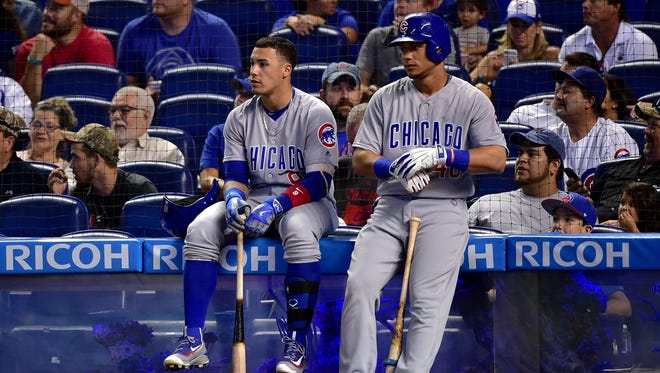 Chicago Cubs second baseman Javier Baez (left) and Chicago Cubs left fielder Willson Contreras (right) both look on from the fish tank as a play was under review during the first inning against theMiami Marlins at Marlins Park.
