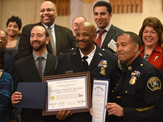 Detroit Police Capt. Harold Rochon, center, with Police Chief James Craig, right, and Councilman Gabe Leland after Rochon accepted an award for his work during a ceremony at Saint Christopher Church in Detroit on May 16, 2015.