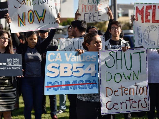 A small group of sanctuary state supporters gather outside the Orange County Board of Supervisors meeting in Santa Ana as supervisors prepare to discuss joining a lawsuit against the state of California on Tuesday.