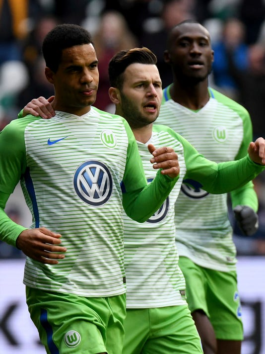 Wolfsburg's Daniel Didavi, left, and teammates Renato Steffen and Josuha Guilavogui, right, celebrate the opening goal during the German Bundesliga soccer match between VfL Wolfsburg and Bayern Munich, in Wolfsburg, northern Germany, Saturday, Feb. 17, 2018.  (Peter Steffen/dpa via AP)