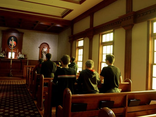 Young men and a priest pray in the Miles Christi's