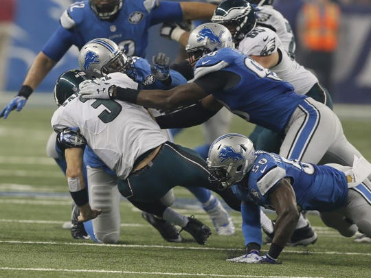Ezekiel Ansah, Devin Taylor and Tahir Whitehead get one of the Lions' six sacks of the Eagles' Mark Sanchez.