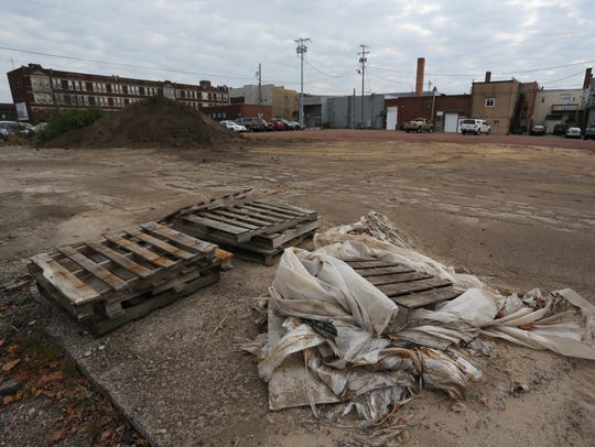 Pallets and plastic sheeting lie on the ground at the