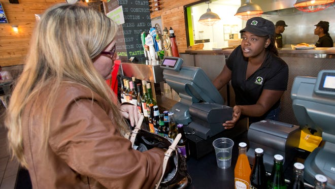 BurgerFi restaurant supervisor Alexis Charles, right, takes an order from Ellisa Horvath of Aventura, at the restaurant in Aventura, Fla.. Companies such as the gourmet hamburger chain BurgerFi plan to nearly double in size from their existing 65 restaurants this year.
