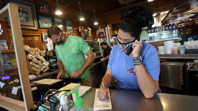 Chase Webb rings up orders while sister Natalie Ramsey takes call-ins at Red Bridge's Barbecue on Friday.