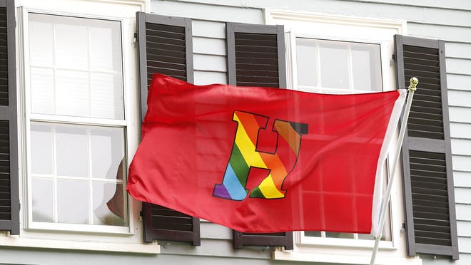 A special Hingham pride flag based on the high school's athletic logo features a rainbow H instead of the traditional white letter, is displayed at a home on Main Street.