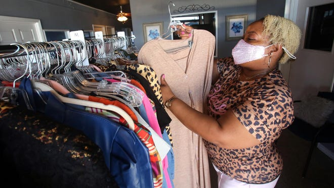 Crystal Kegler arranges clothing at Danielle's Boutique in Shelby.