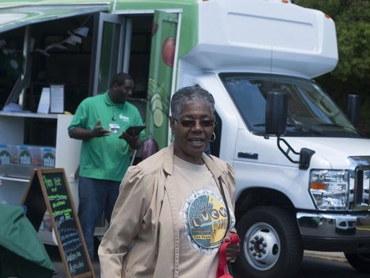 Juanita Hicks of Camden walks home with two bags of produce purchased at the Virtua Mobile Farmers Market outside Virtua Camden. The health system is offering free produce to furloughed government workers.