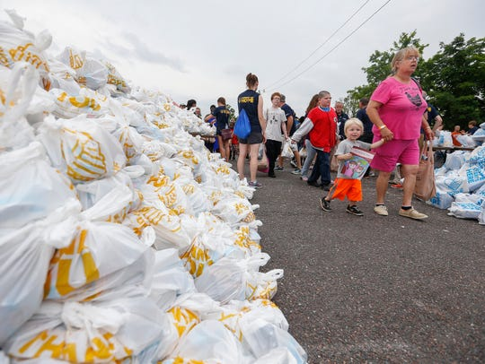 Members of the community receive groceries from volunteers during Convoy of Hope's Day of Kindness at the Ozark Empire Fairgrounds on Saturday, June 2, 2018.  Caption Override