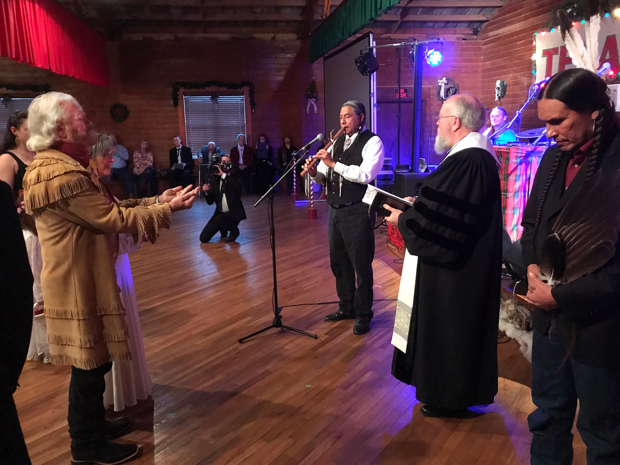 Hands out, Michael Martin Murphey and, at his side, Cynthia Tune, accept the spirit flowing from the flute music of Terry Tsotigh. Co-officiants Dale Schultz and Moses Brings Plenty listen.
