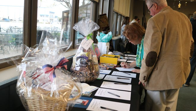 Guests look over items for bid at 'Starry, Starry Night Live and Silent Auction,' hosted by the Kiwanis Club at the Port Clinton Yacht Club, on Saturday night. The fundraiser aimed to raise around $30,000 for the STARR Project.