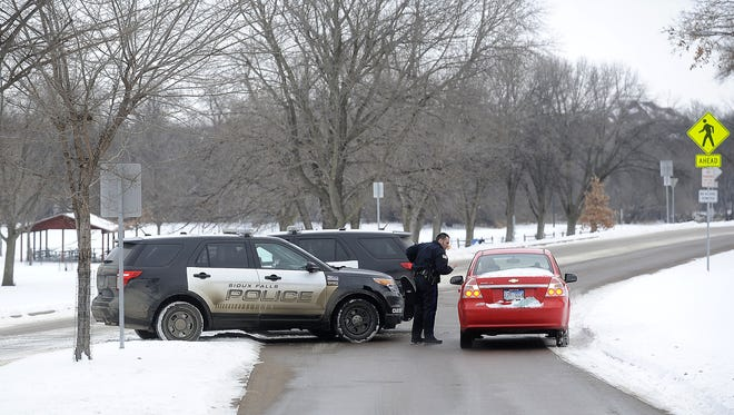 Police ask visitors to leave Tuthill Park as they block the entrance along Cliff Avenue in Sioux Falls, S.D., Friday, Jan. 2, 2015. A suspect was involved in a shooting Thursday night with a police officer at Tuthill Park.