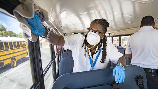 A bus attendant cleans surfaces inside a school bus at a Palm Beach County School District transportation facility in March. Buses were being wiped down to help prevent the spread of novel coronavirus.