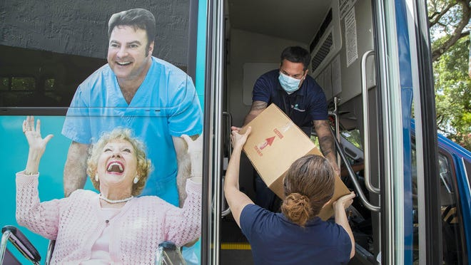 Volen Center employees Nancy Vaughn and Joe Iovino transfer boxes filled with 14 meals to buses to be delivered to seniors on Tuesday. To deal with challenges of coronavirus, more seniors need meals but serving them cafeteria style at the Volen Center in Boca Raton is out.