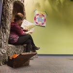 """Reading """"Whose Tail is This,"""" Howell Carnegie District Library youth services librarian Laura Grabijas leads an early literacy class for preschoolers. Listening raptly are, from left, Axel Daavettila, Landon and Eli Halonen and Tricia Kantola."""